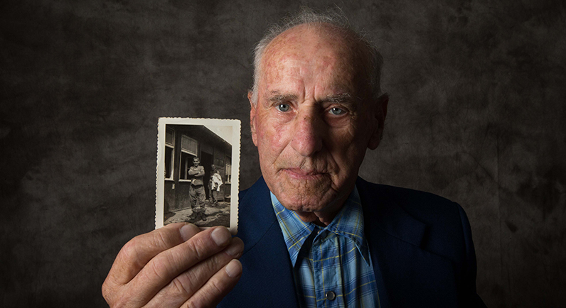 Holocaust survivor Jack Meister with a photograph of himself, taken at the liberation of Buchenwald in 1945