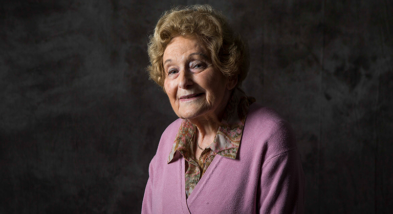 Woman wearing pink cardigan looking at the camera, Holocaust survivor Beate Stricker