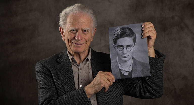 Holocaust survivor Maurice Linker holding a photograph of himself as a child