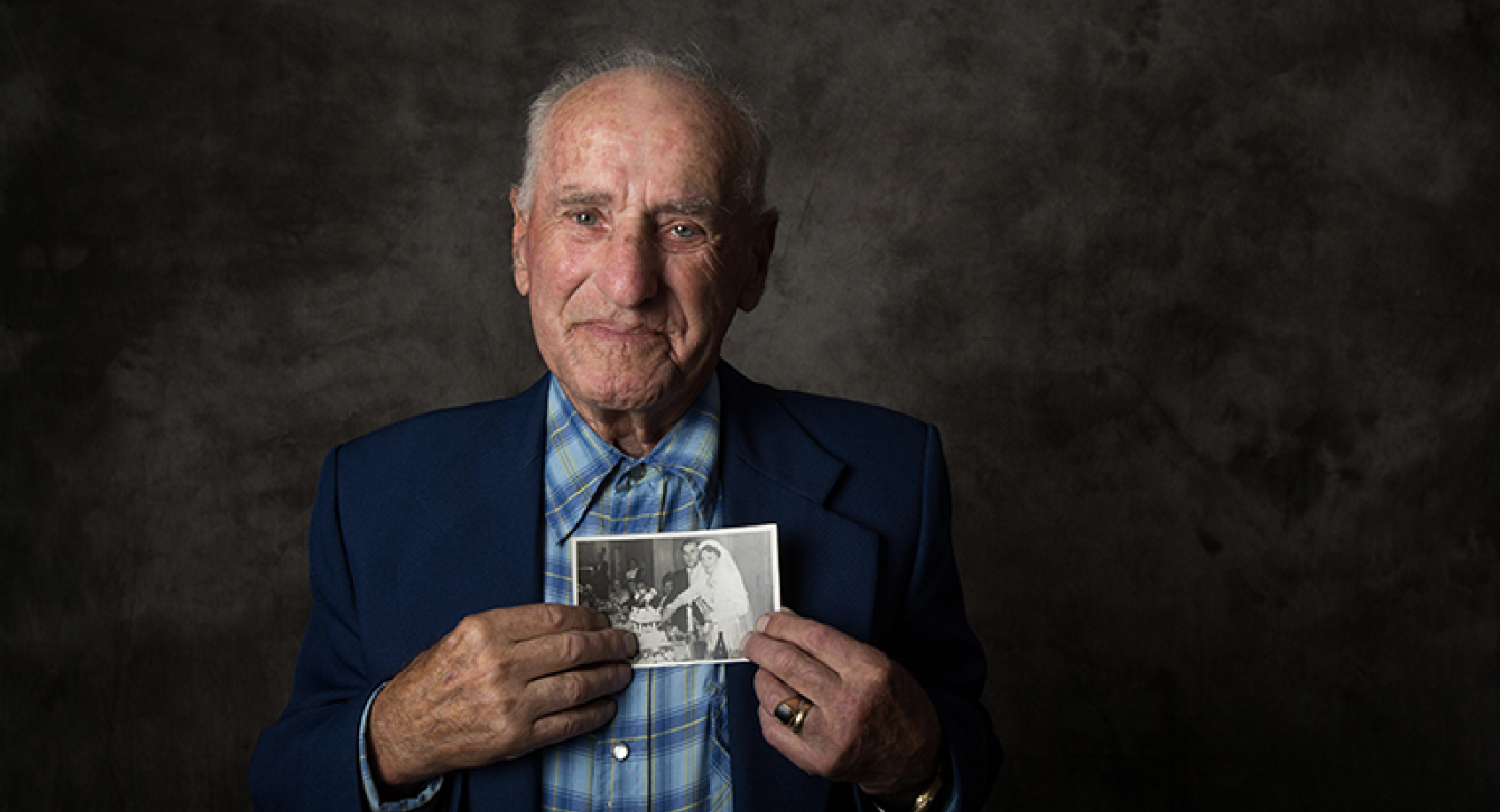 Photograph of Holocaust survivor Jack Meister holding a photo of himself and his wife at their wedding