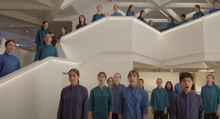 Youth wearing blue and green clothing standing in Sydney Jewish Museum space, singing