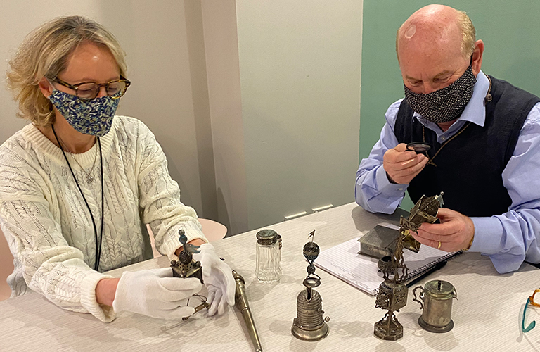 Woman and man wearing masks, handling silver Judaica items