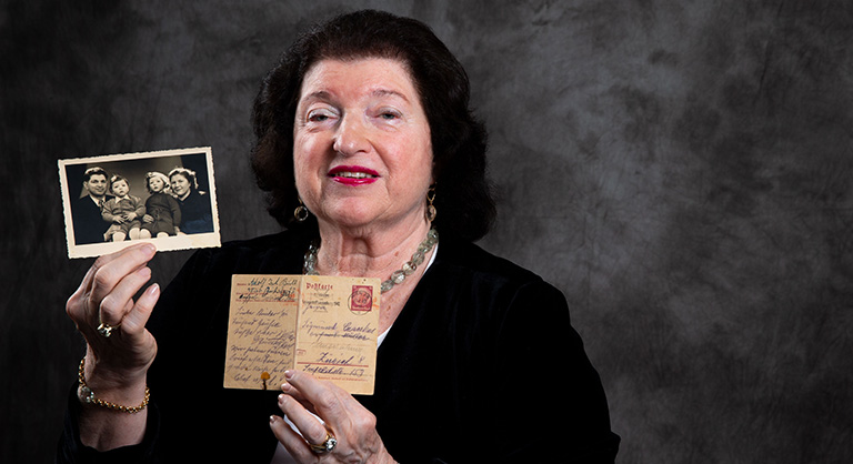 Photograph of Holocaust survivor Alice Loeb holding a photograph and a document