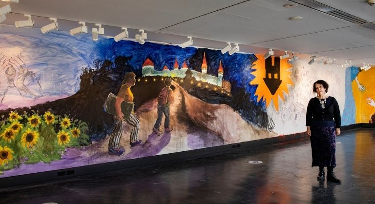Artist Wendy Sharpe, standing in front of a mural fragment featuring Kamianets Podilskyi