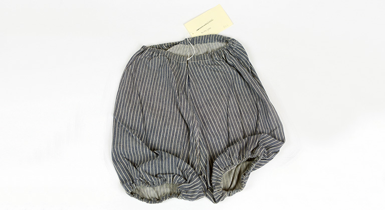 Photograph of blue and white striped bloomers with yellow tage denoting museum number
